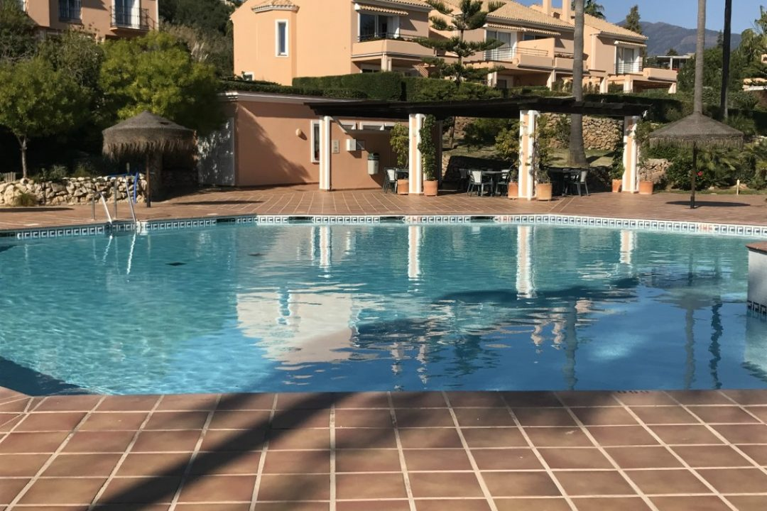 Outdoor pool with covered dining area in the Paraiso Park complex in Benahavis