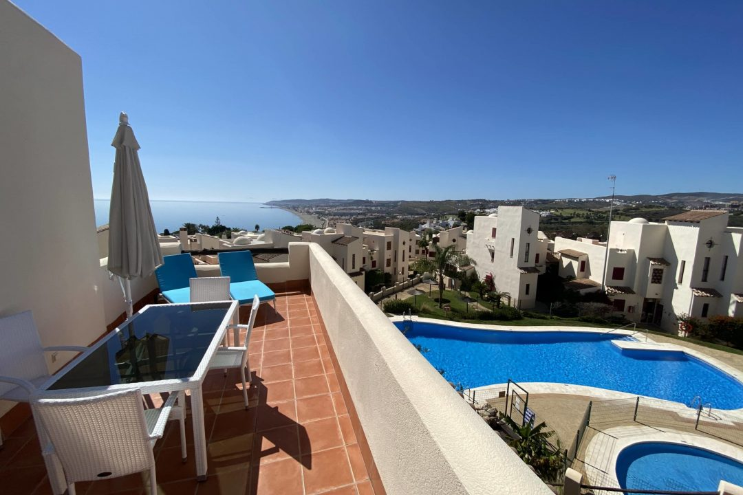 Outdoor balcony overlooking the pool area and stunning views of the beach at 37 Casares, Casares