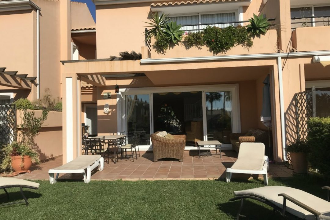 Outdoor private terrace area with sun loungers and outdoor dining area at Paraiso Park Town House, Benahavis