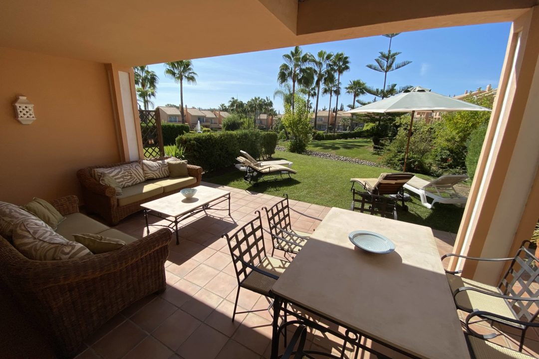 Outdoor private terrace with lounge area and dining at Paraiso Park Town House, Benahavis